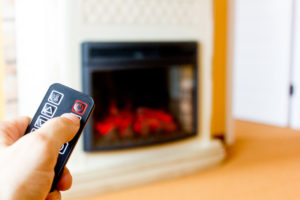 Person operates electric fireplace with remote control