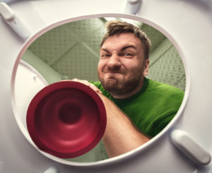 man plunges toilet and grimaces
