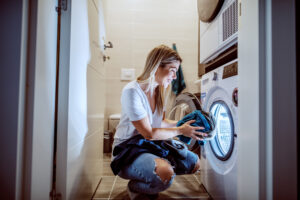 Woman uses energy efficient clothes dryer