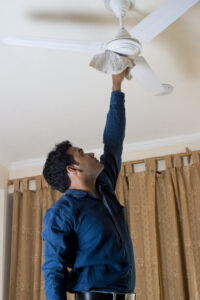 Image shows a man trying to clean a ceiling fan with a cloth