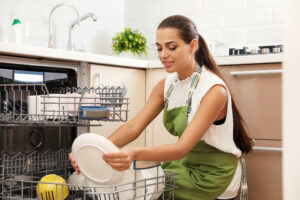 Image shows woman loading a dishwasher