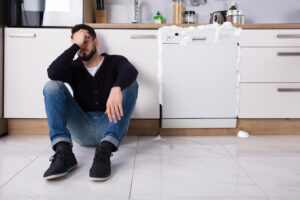 Image of upset man as dishwasher overflows with soap behind him