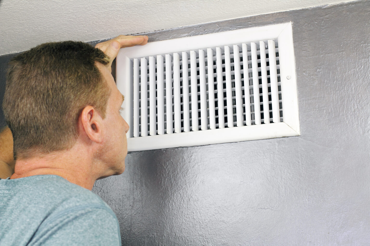 image of a man inspecting an air vent
