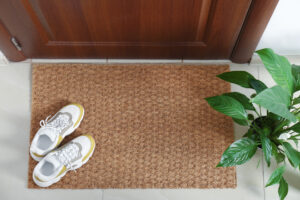 Image of shoes placed by front door mat